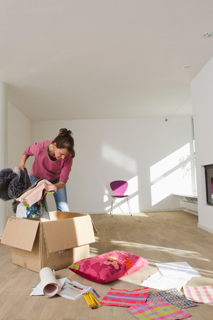 cardboard only: Woman unpacking from cardboard box LANG_EVOIMAGES