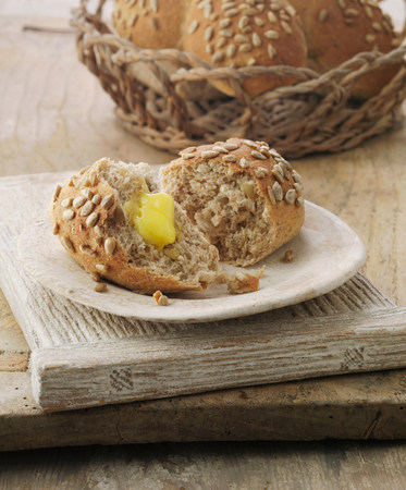 Sunflower and honey wheat sheaf bread roll with butter