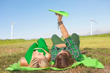 untruth: Young couple lying in field,man holding paper aeroplane LANG_EVOIMAGES
