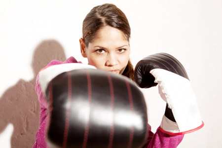 athleticism: Young woman wearing boxing gloves