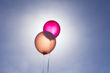 Translucent balloons against blue sky