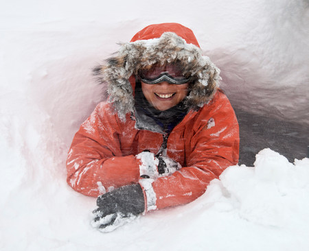 Woman crawling out of snow cave