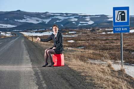 recuperating: Woman sitting on petrol can at roadside hitchhiking