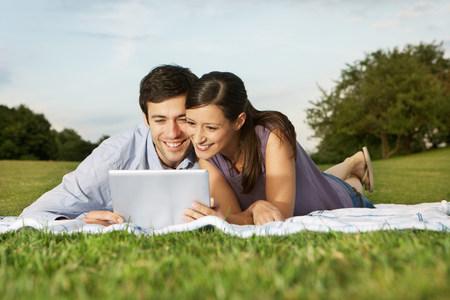 materialism: Mid adult couple using digital tablet
