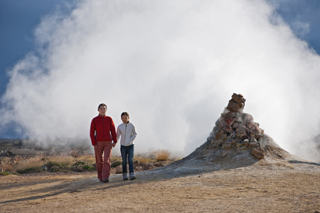 Mother and daughter by spewing geyser