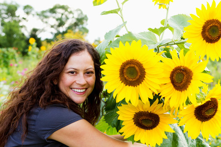 Portrait of young woman and sunflowers in allotment LANG_EVOIMAGES