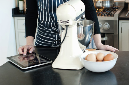 worktops: Woman using digital tablet to check recipe