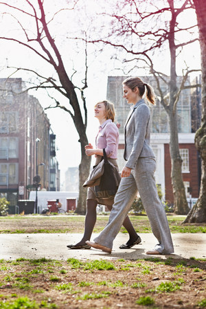 Two businesswomen walking on path in park LANG_EVOIMAGES