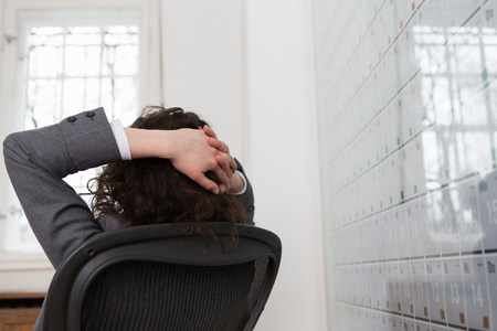 chillout: Woman sitting in office chair in front of large wall calendar