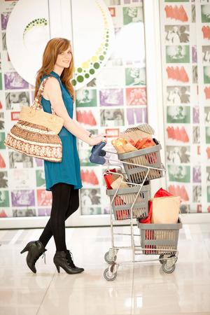 Woman pushing shopping cart in mall