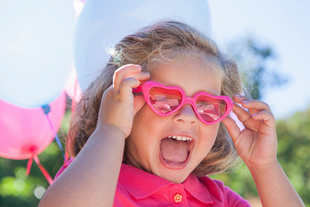 Girl wearing pink heart shaped sunglasses LANG_EVOIMAGES