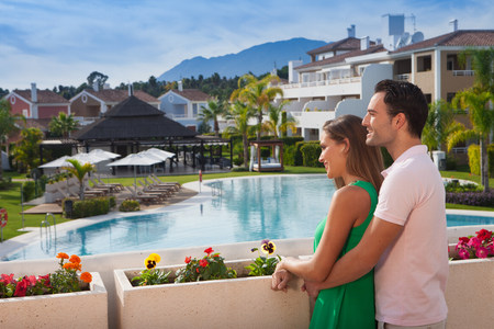 honeymooner: Young couple looking at view at holiday resort LANG_EVOIMAGES