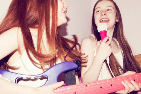 jesting: Two girls playing guitar and singing into microphone in bedroom LANG_EVOIMAGES