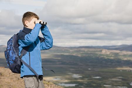 Boy examining landscape with binoculars