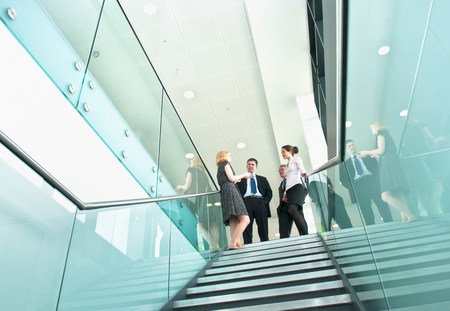 60 64 years: Colleagues standing on staircase in office building