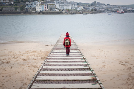 admired: Rear view of boy standing on pier overlooking sea