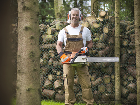 grays: Man holding chain saw by firewood