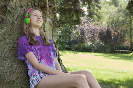 Girl listening to headphones in park LANG_EVOIMAGES