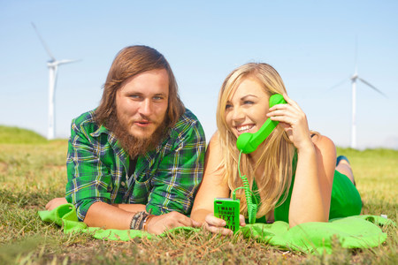 Young couple lying in field,woman on green cell phone