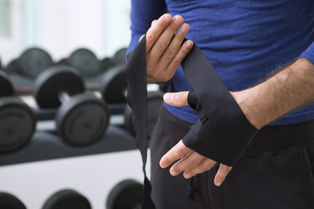 appendage: Boxer wrapping his hands in gym
