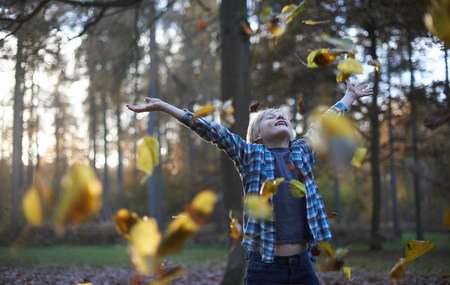Boy throwing leaves in air