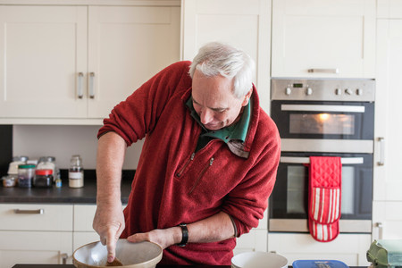 gloved: Senior male using wooden spoon in mixing bowl LANG_EVOIMAGES