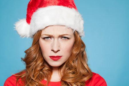 Woman wearing santa hat,frowning