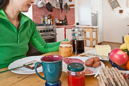 low section: Woman having breakfast in chalet kitchen LANG_EVOIMAGES