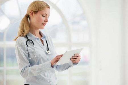 authoritative woman: Portrait of female doctor with stethoscope and digital tablet LANG_EVOIMAGES