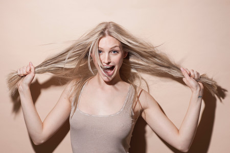 Portrait of young blonde woman holding hair and screaming LANG_EVOIMAGES