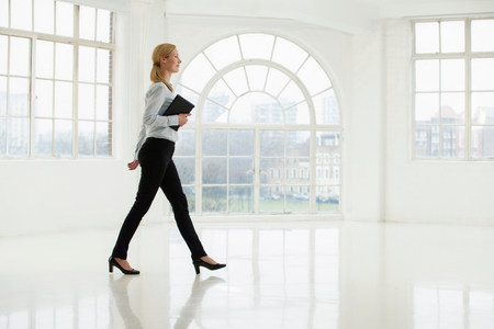 authoritative woman: Businesswoman walking in sparse white room LANG_EVOIMAGES