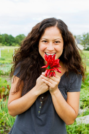 Portrait of young woman holding  crop of red chillies in allotment