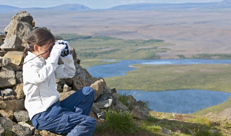 Girl examining landscape with binoculars