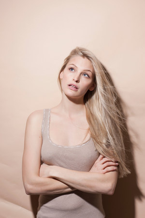 fedup: Young blonde woman looking up with arms crossed