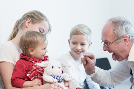 age 10 12 years: Child on sisters lap being examined by doctor