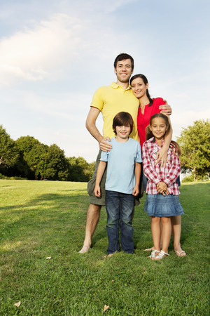 Portrait of family with two children standing on grass