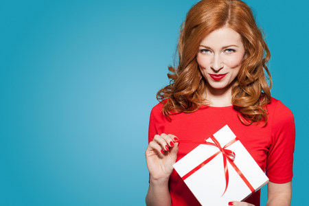 Woman holding white gift box with red bow LANG_EVOIMAGES