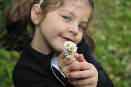 Girl holding bunch of daisies LANG_EVOIMAGES