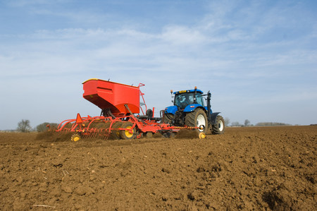 farmyards: Tractor pulling equipment to plant seeds in field LANG_EVOIMAGES