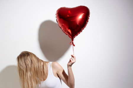 Woman with red heart-shaped balloon LANG_EVOIMAGES