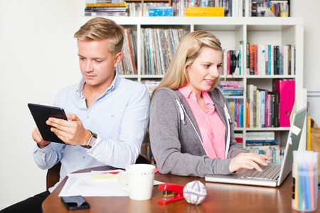 pubertad: Estudiantes que trabajan en la computadora portátil y la tableta digital