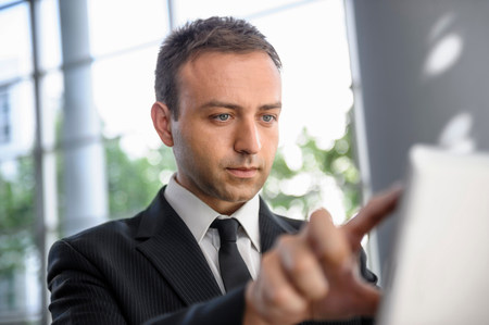 handheld device: Businessman interacting with digital tablet screen
