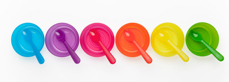 Colourful plastic spoons and bowls in a row