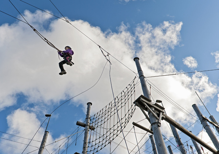jeopardizing: Girl swinging on rope course LANG_EVOIMAGES