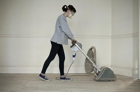 exerting: Mature woman sanding floor of new home