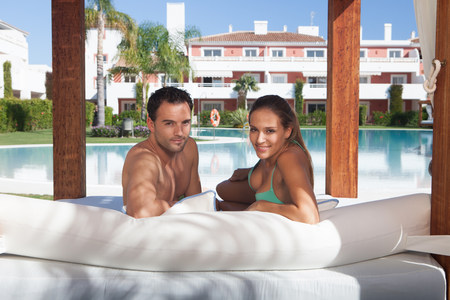 honeymooner: Young couple relaxing on sunlounger at holiday resort