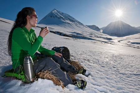 Mature woman sitting with a hot drink in snowy mountains,Skidadalur,Dalvik,Iceland