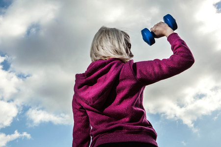 Young woman using hand weights LANG_EVOIMAGES