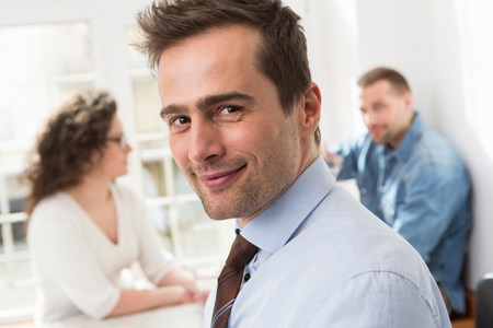 Mature man smiling at camera,mid adults in background LANG_EVOIMAGES