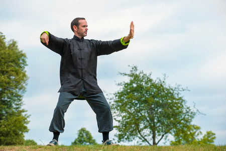 Mature man performing Tai Chi in countryside
